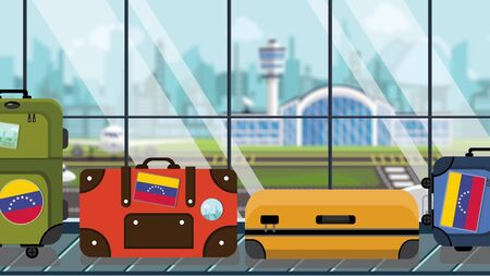 Suitcases with Venezuelan flag stickers on baggage carousel in airport, close-up. Tourism in Venezuela related illustration Stock Photo