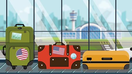 Luggage with American flag stickers on baggage carousel in airport, close-up. USA tourism related illustration