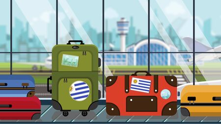 Suitcases with Uruguayan flag stickers on baggage carousel in airport, close-up. Tourism in Uruguay related illustration