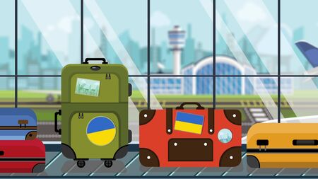 Suitcases with Ukrainian flag stickers on baggage carousel in airport, close-up. Tourism in Ukraine related illustration