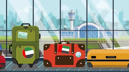 Suitcases with UAE flag stickers on baggage carousel in airport, close-up. Tourism in United Arab Emirates related illustration Stock Photo