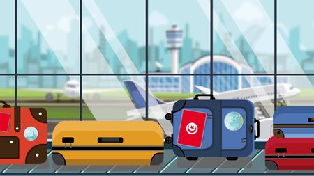 Luggage with Tunisian flag stickers on baggage carousel in airport, close-up. Tourism in Tunisia related illustration Stock Photo