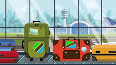 Suitcases with Tanzanian flag stickers on baggage carousel in airport, close-up. Tourism in Tanzania related illustration