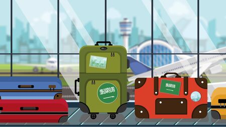 Suitcases with Saudi Arabia flag stickers on baggage carousel in airport, close-up. Tourism related illustration