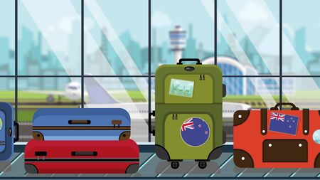Suitcases with New Zealand flag stickers on baggage carousel in airport, close-up. Tourism related illustration
