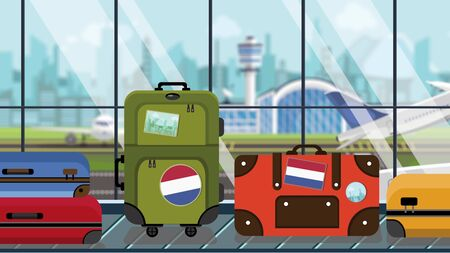 Baggage with Netherlands flag stickers on carousel in airport, close-up. Travel related illustration Imagens