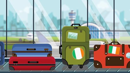 Suitcases with Irish flag stickers on baggage carousel in airport, close-up. Tourism in Ireland related illustration