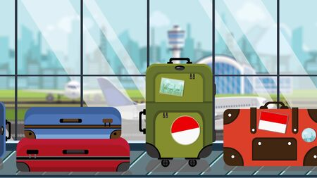 Luggage with Indonesian flag stickers on baggage carousel in airport, close-up. Tourism in Indonesia related illustration Imagens