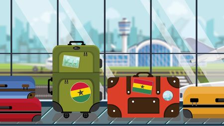 Suitcases with Ghanaian flag stickers on baggage carousel in airport, close-up. Travel to Ghana related illustration Stock Photo