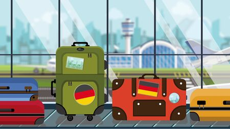 Luggage with Gegman flag stickers on baggage carousel in airport, close-up. Tourism in Germany related illustration