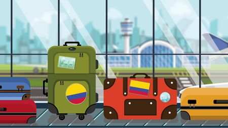Suitcases with Colombian flag stickers on baggage carousel in airport, close-up. Tourism in Colombia related illustration