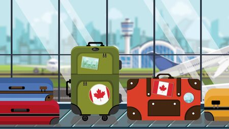 Suitcases with Canada flag stickers on baggage carousel in airport, close-up. Canadian tourism related illustration