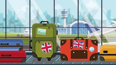 Suitcases with UK flag stickers on baggage carousel in airport, close-up. British tourism related illustration