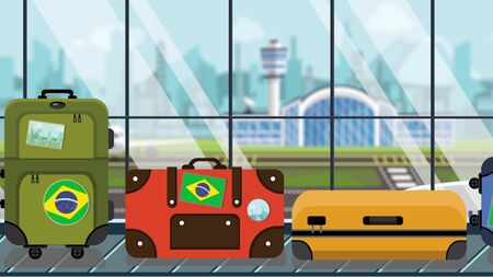 Luggage with Brazil flag stickers on baggage carousel in airport, close-up. Brazilian tourism related illustration