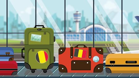 Suitcases with Belgian flag stickers on baggage carousel in airport, close-up. Tourism in Belgium related illustration