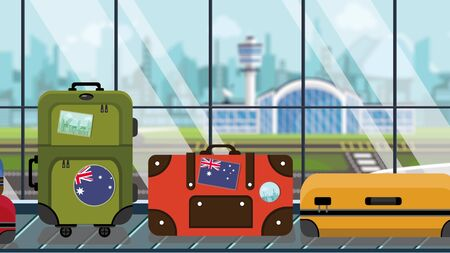 Baggage with Australia flag stickers on carousel in airport, close-up. Australian tourism related illustration