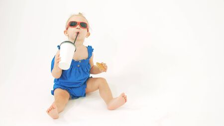 Cool baby girl wearing sunglasses drinks from paper cup with a straw against white background