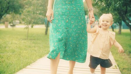Cheerful baby girl and her mum walk together in the park on a summer day 版權商用圖片 - 129817753