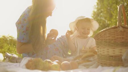 Cheerful little baby girl and her mom having picnic on a summer day