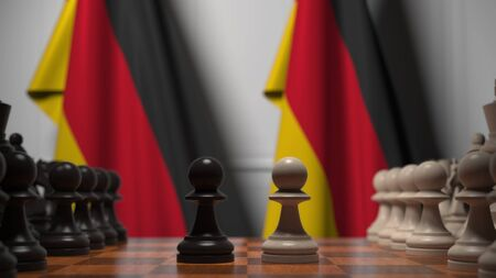 Flags of Germany behind chess board. The first pawn moves in the beginning of the game. Political rivalry conceptual 3D rendering