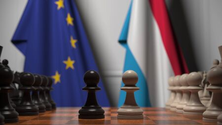 Flags of the EU and Luxembourg behind chess board. The first pawn moves in the beginning of the game. Political rivalry conceptual 3D rendering