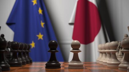 Flags of the EU and Japan behind chess board. The first pawn moves in the beginning of the game. Political rivalry conceptual 3D rendering