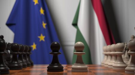 Flags of the EU and Hungary behind chess board. The first pawn moves in the beginning of the game. Political rivalry conceptual 3D rendering