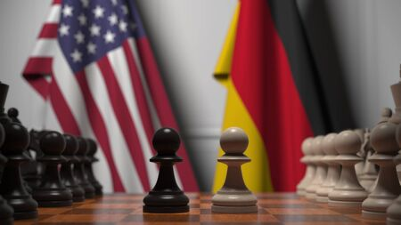 Flags of United States and Germany behind chess board. The first pawn moves in the beginning of the game. Political rivalry conceptual 3D rendering