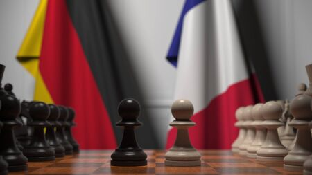 Flags of Germany and France behind chess board. The first pawn moves in the beginning of the game. Political rivalry conceptual 3D rendering