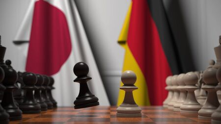Flags of Japan and Germany behind chess board. The first pawn moves in the beginning of the game. Political rivalry conceptual 3D rendering