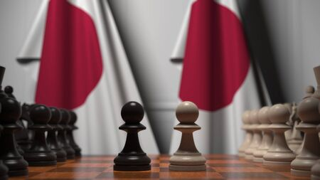 Flags of Japan behind chess board. The first pawn moves in the beginning of the game. Political rivalry conceptual 3D rendering Stockfoto