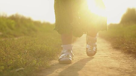 Steadicam shot of baby girl walking along rural field pathway on a sunny day, feet close-up