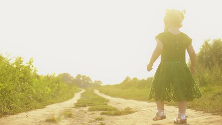 Baby girl walking along rural field pathway on a sunny summer evening