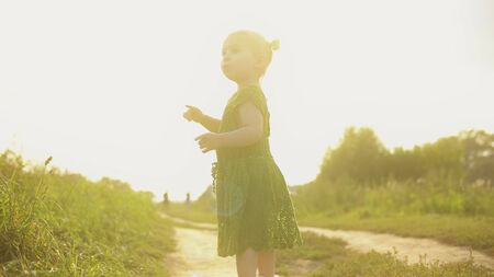Curious baby girl walking along rural field pathway on a sunny summer evening Foto de archivo