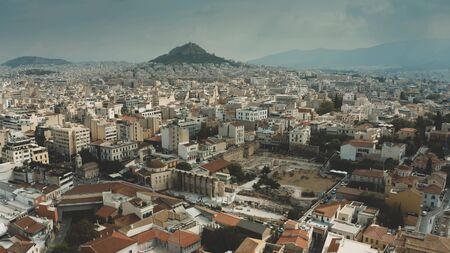 Aerial view of the cityscape of Athens, Greece. Flight from the Acropolis towards the Lycabettus Hill