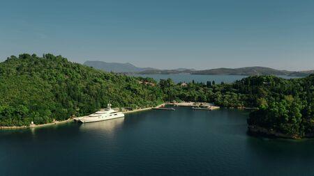 LEFKADA, GREECE - SEPTEMBER 21, 2019. Aerial shot of Feadship luxury motor yacht Anna docked at Skorpios island Editorial