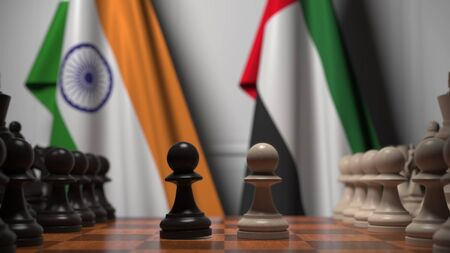 Flags of India and UAE behind pawns on the chessboard. Chess game or political rivalry related 3D rendering