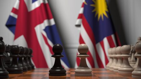 Flags of Great Britain and Malaysia behind pawns on the chessboard. Chess game or political rivalry related 3D rendering
