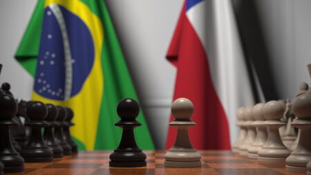 Flags of Brazil and Chile behind pawns on the chessboard. Chess game or political rivalry related 3D rendering Фото со стока