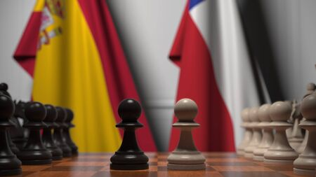 Flags of Spain and Chile behind pawns on the chessboard. Chess game or political rivalry related 3D rendering