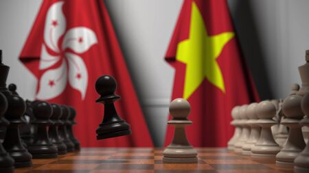 Flags of Hong Kong and Vietnam behind pawns on the chessboard. Chess game or political rivalry related 3D rendering Stock Photo