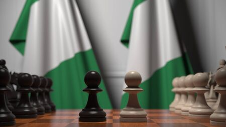 Flags of Nigeria behind pawns on the chessboard. Chess game or political rivalry related 3D rendering Stock Photo