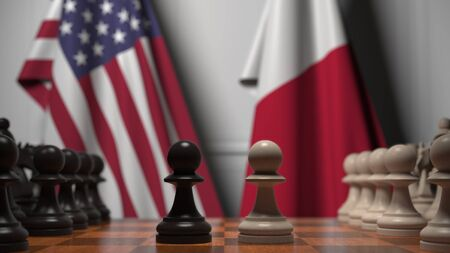 Flags of USA and Malta behind pawns on the chessboard. Chess game or political rivalry related 3D rendering 写真素材