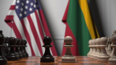 Flags of USA and Lithuania behind pawns on the chessboard. Chess game or political rivalry related 3D rendering