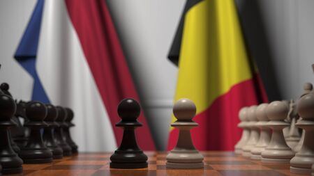Flags of Netherlands and Belgium behind pawns on the chessboard. Chess game or political rivalry related 3D rendering