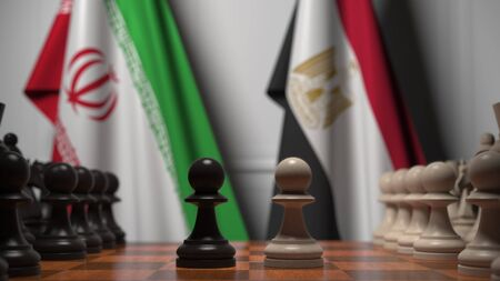 Flags of Iran and Egypt behind pawns on the chessboard. Chess game or political rivalry related 3D rendering 免版税图像