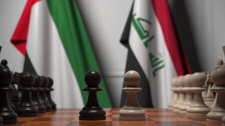 Flags of the United Arab Emirates and Iraq behind pawns on the chessboard. Chess game or political rivalry related 3D rendering