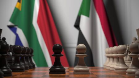 Flags of South Africa and Sudan behind pawns on the chessboard. Chess game or political rivalry related 3D rendering 免版税图像