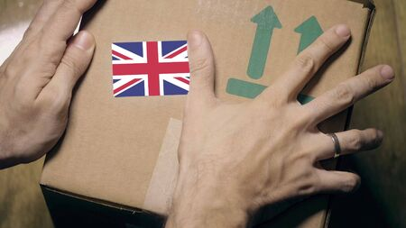 Warehouse worker places sticker with flag of Great Britain on the box. British import or export