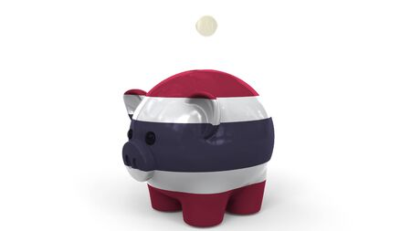 Coins fall into piggy bank painted with flag of Thailand. National banking system or savings related conceptual 3D rendering 写真素材